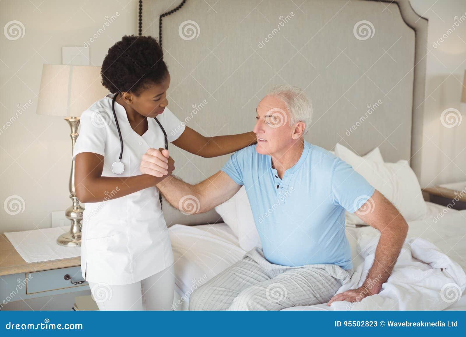 Soignez examiner un homme supérieur sur le lit dans la chambre à coucher