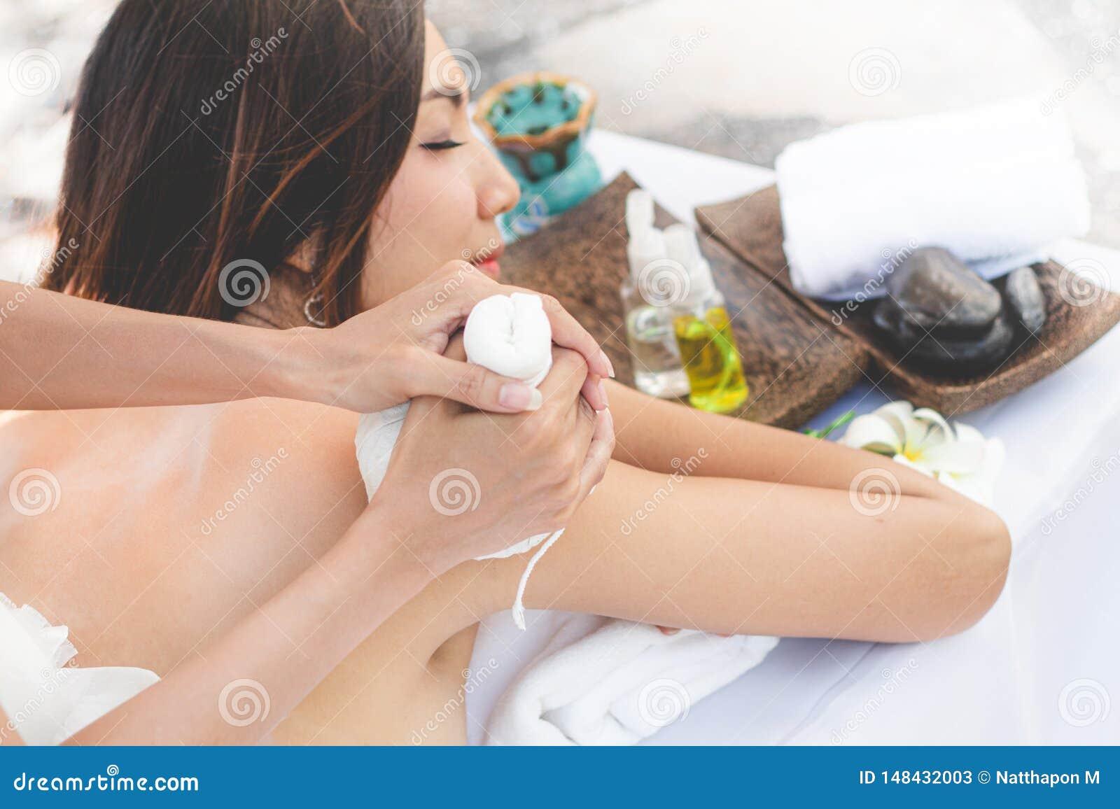 Soin de fuselage Jeune femme asiatique ayant le massage avec les boules de fines herbes chaudes pour la relaxation profonde
