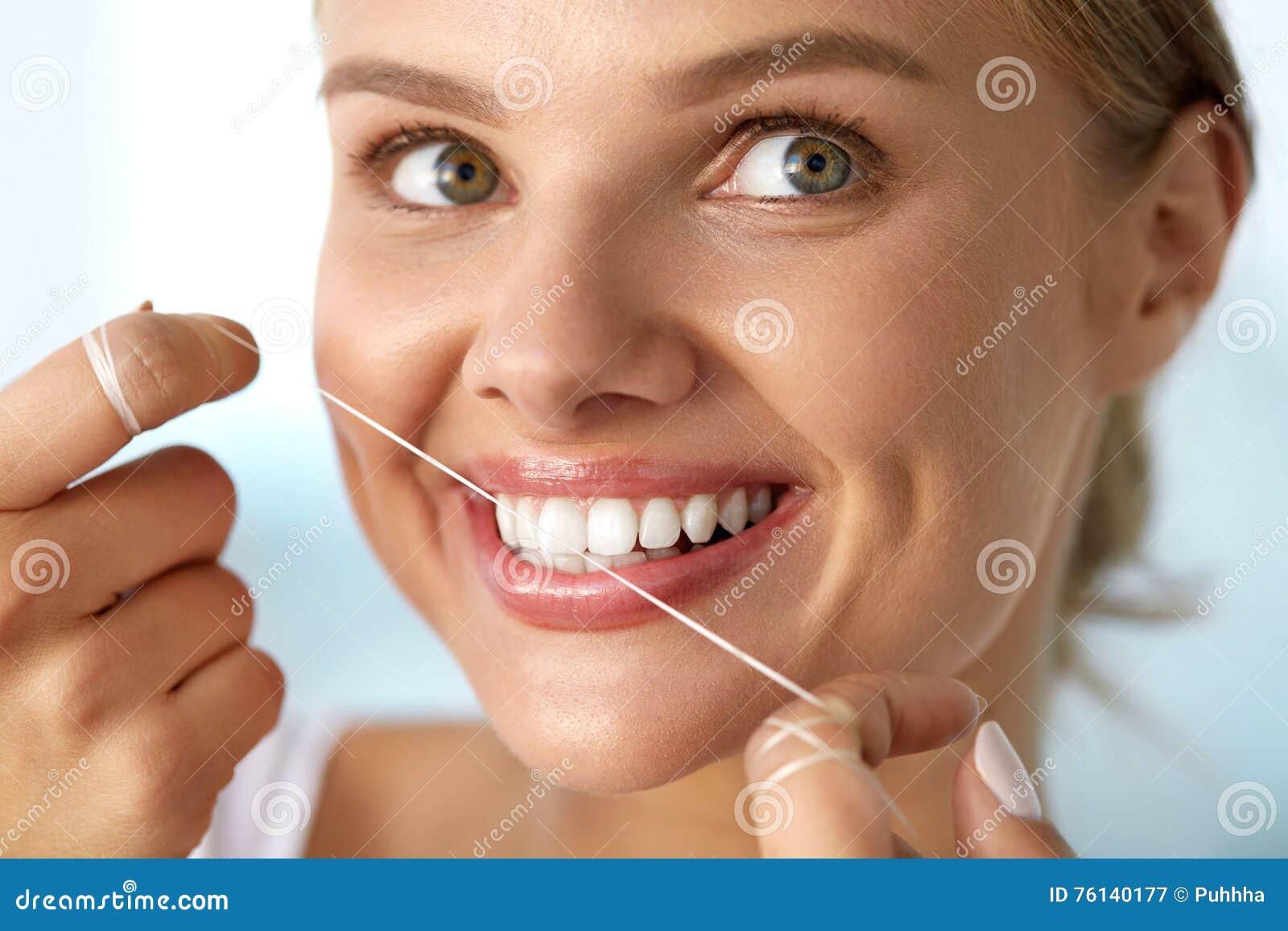 Soin dentaire Femme avec le beau sourire utilisant la soie pour des dents