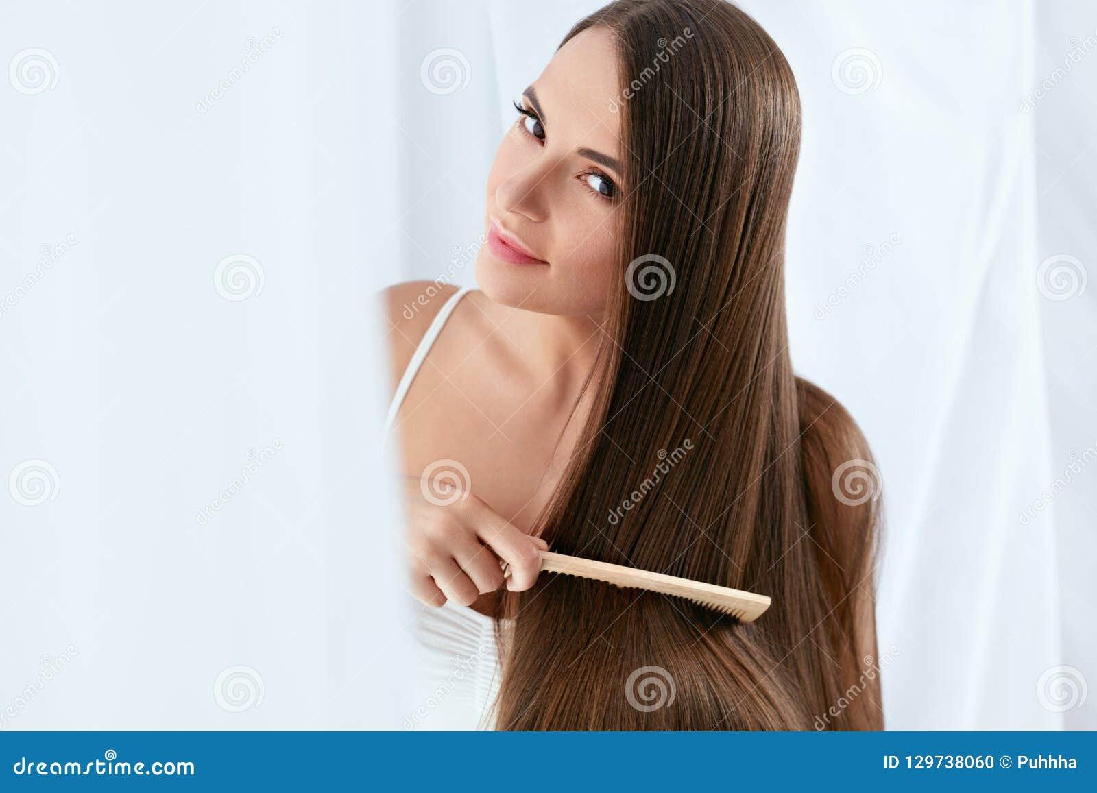 Soins capillaires de beauté Belle femme peignant de longs cheveux naturels