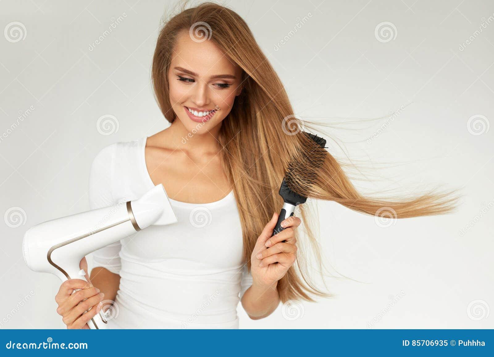 Soins capillaires Femme séchant de beaux longs cheveux utilisant le dessiccateur