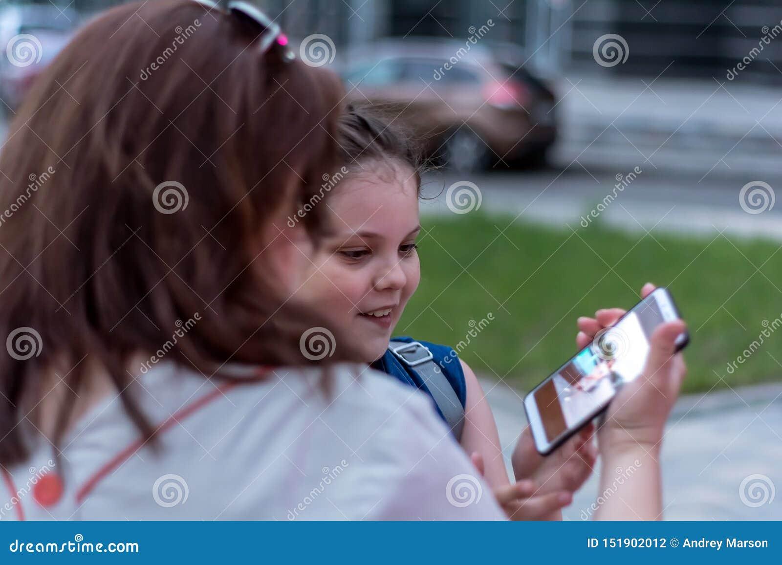 Soir?e d ?t? vacances Photo gentille de montre de mère et de fille sur le smartphone