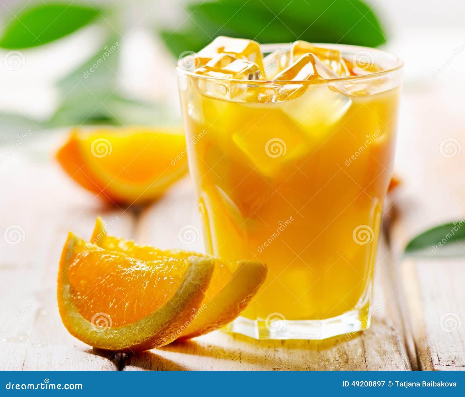 Sok pomarańczowy z świeżymi owoc na drewnianym tle
