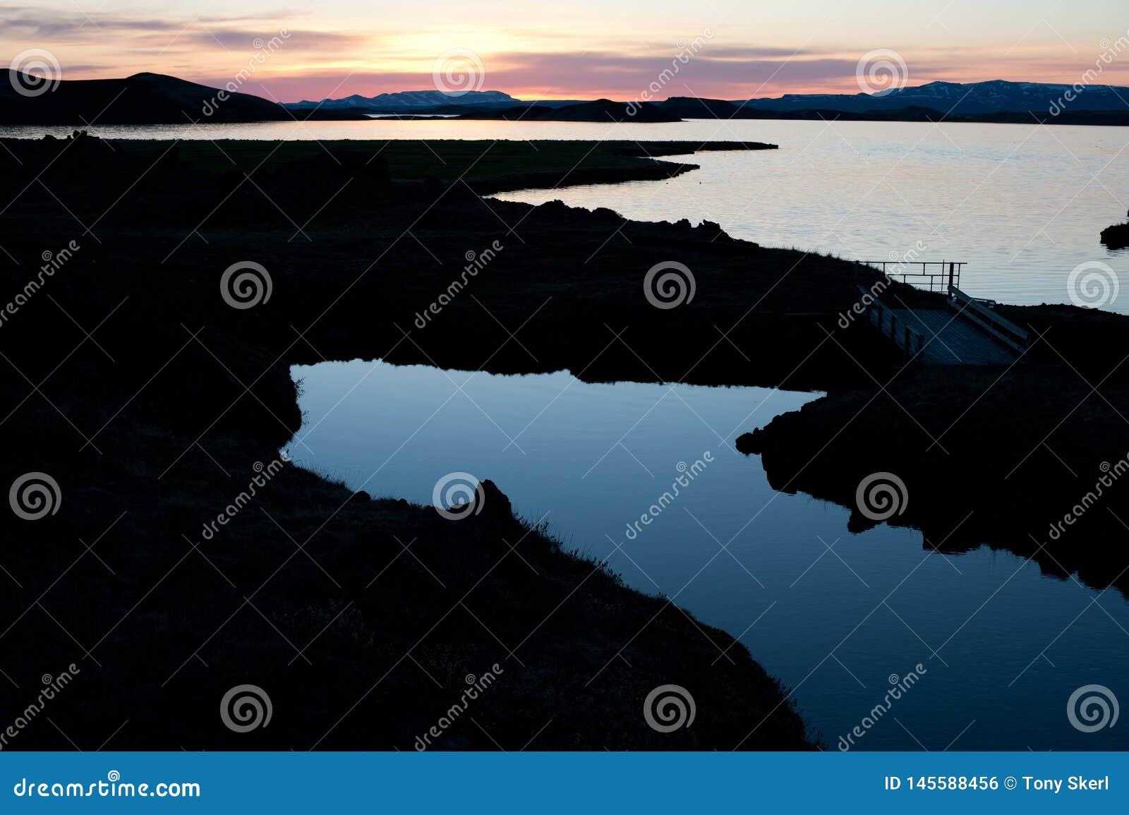 Sol da meia-noite em Islândia com lago Myvatn