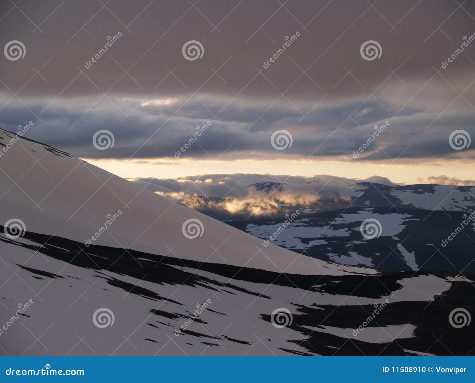 Sol da meia-noite sobre as montanhas nevado