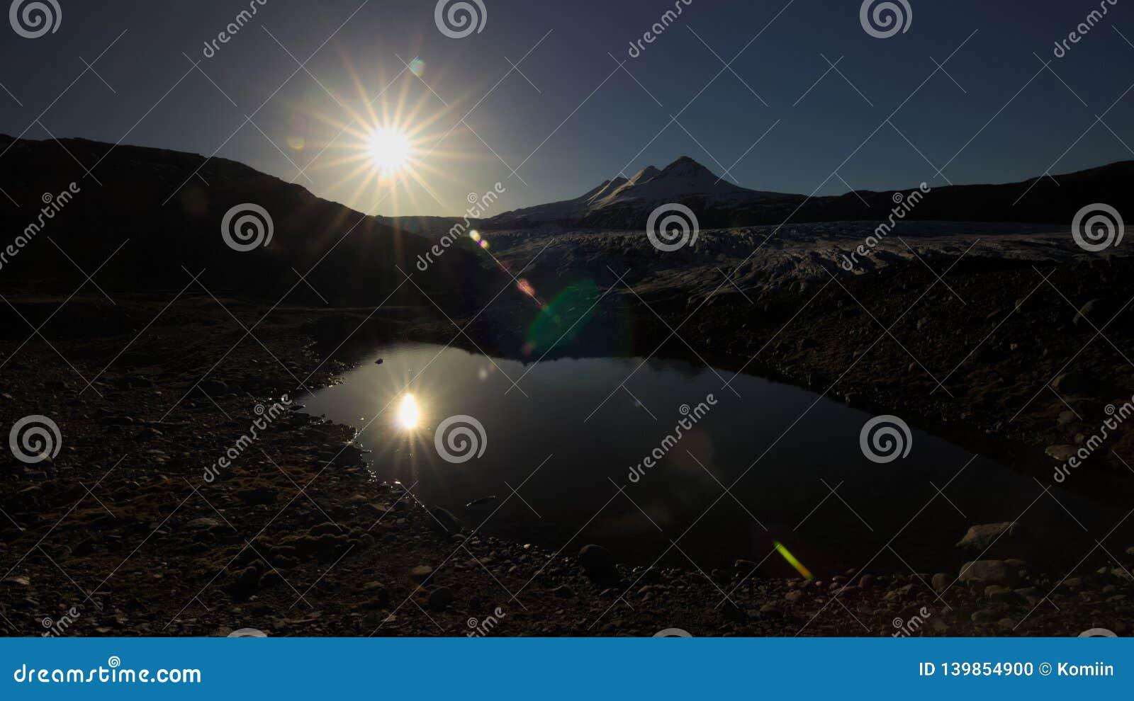Sol da tarde acima da geleira e da lagoa
