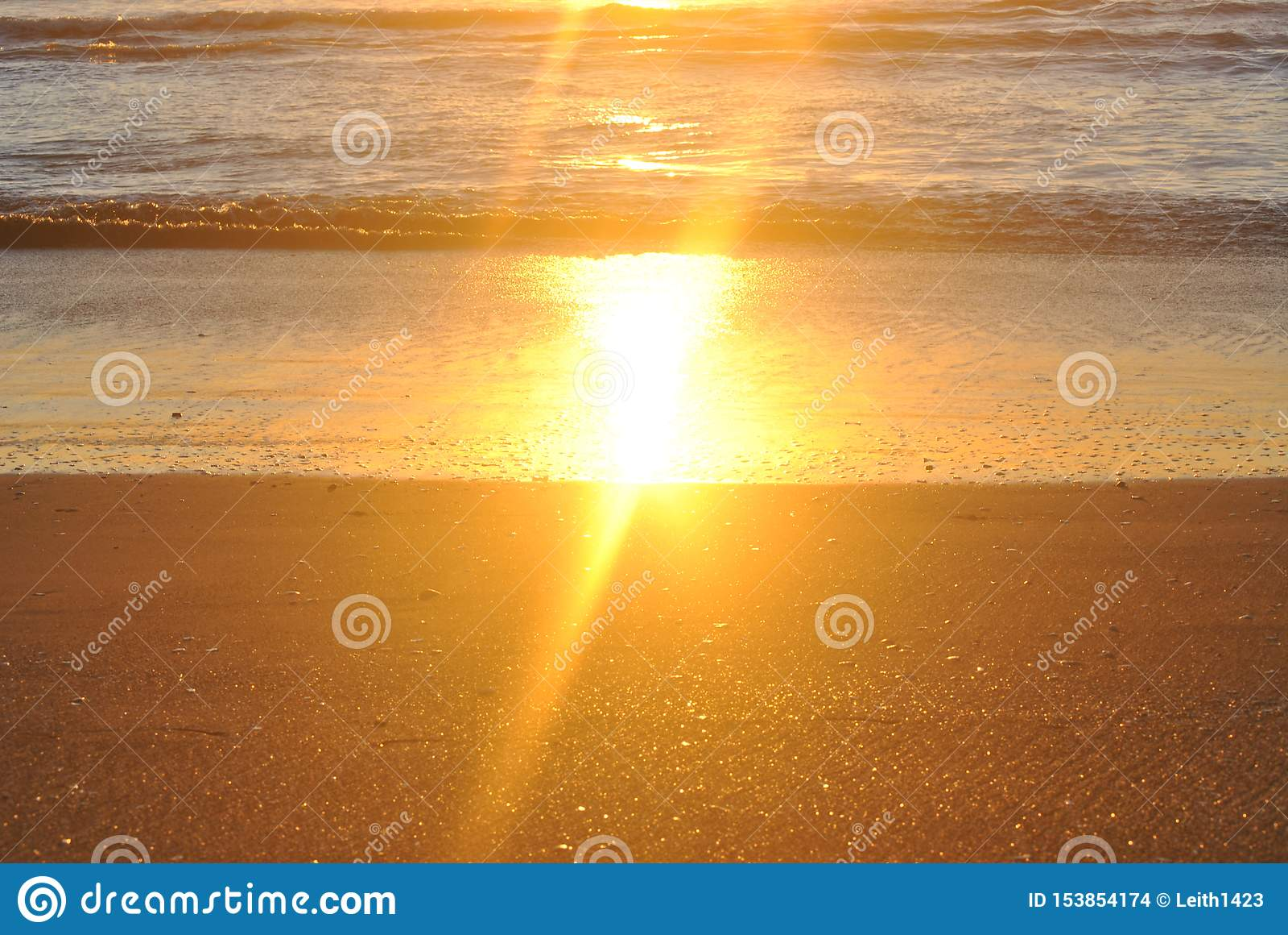 Sol de oro que refleja de la arena mojada