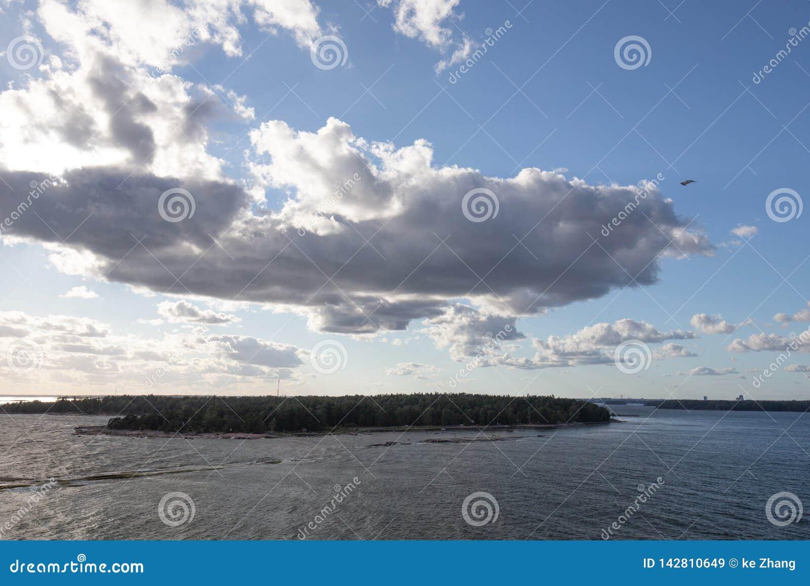 Sol som bryter till och med moln över vatten