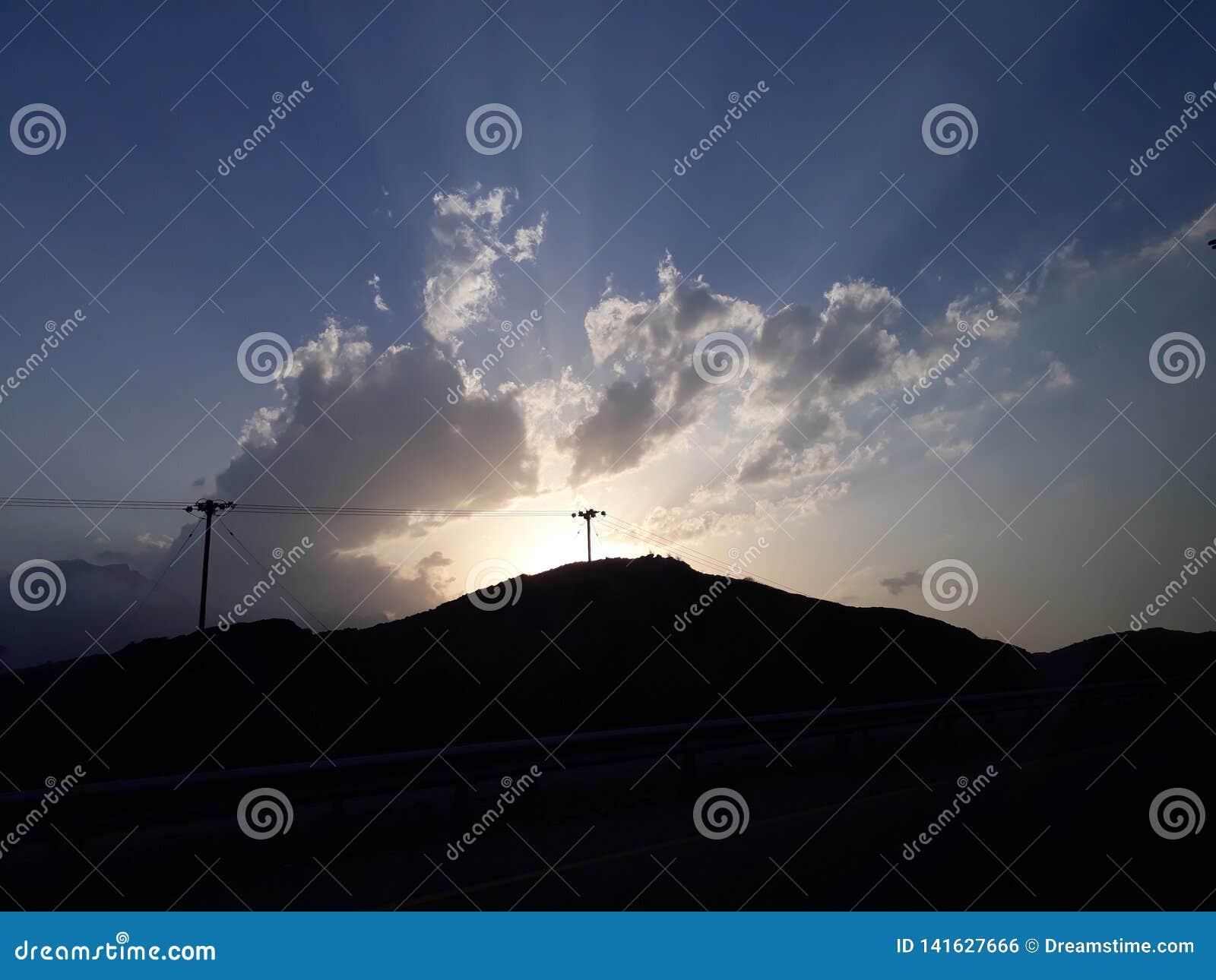 Sol som försöker att fördela dess ljus, medan moln försöker att täcka det De solstrålar ser härliga