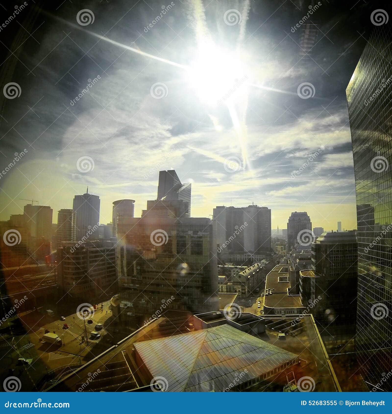 Sol som kikar i himlen över affärsmitten av en stad