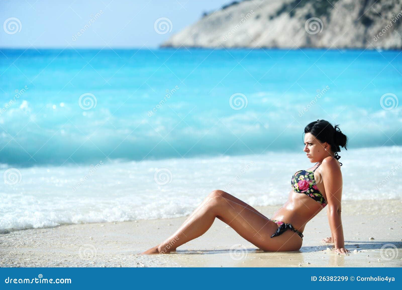 Sol trigueno atractivo de la muchacha que broncea en una playa exótica