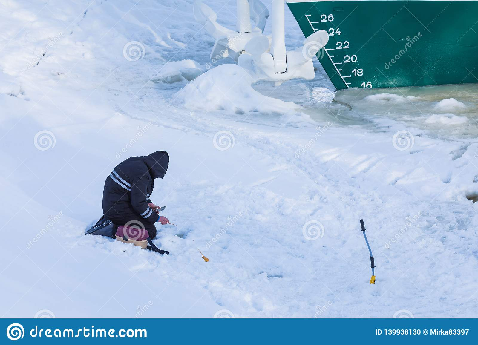 Solamente el pescador que se sienta en el hielo y la nieve del río del invierno en el fondo de la nave