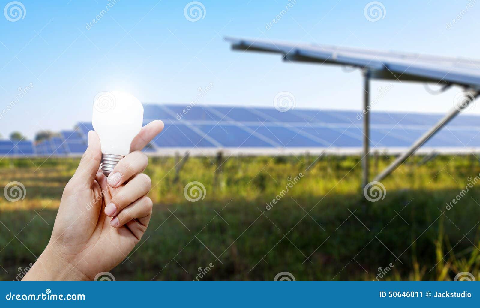 Solar Energy Panels And Light Bulb In Hand Energy Stock