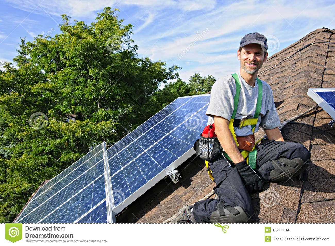 Man installing alternative energy photovoltaic solar panels on roof.