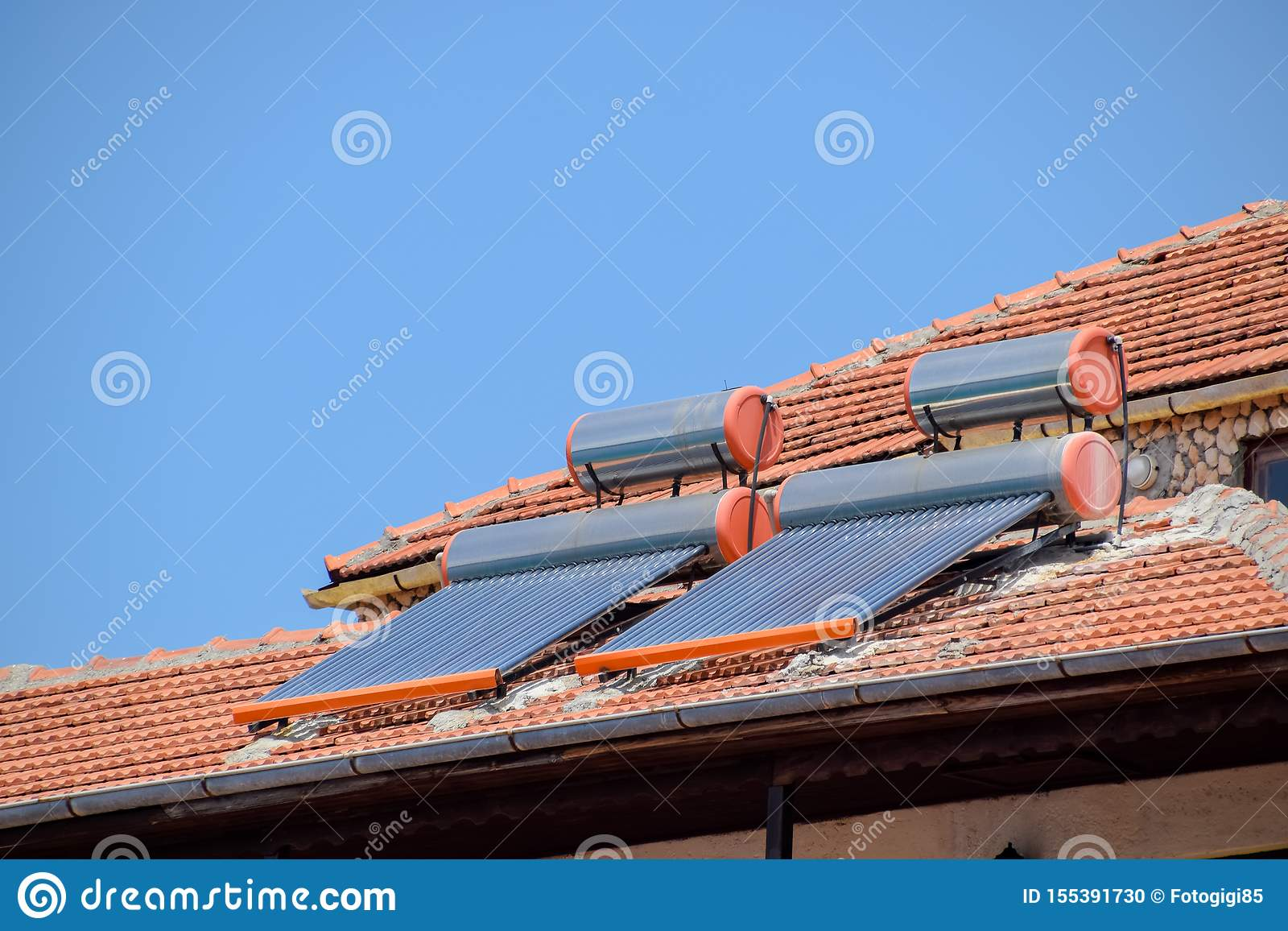 solar panels and barrels for heating water on roof of the house with clay tiles