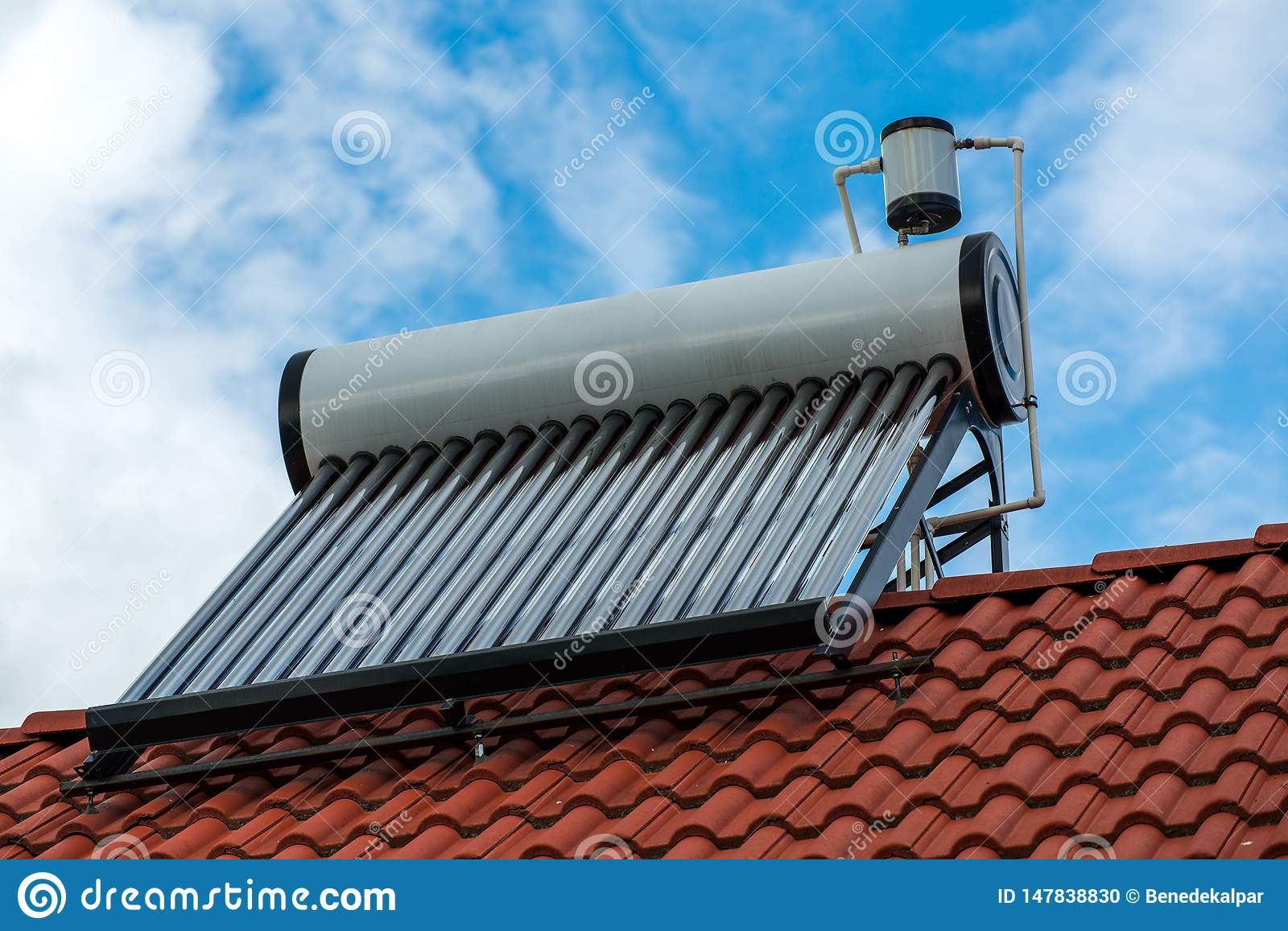 Solar water heater boiler on residentual house rooftop, blue sky with white clouds