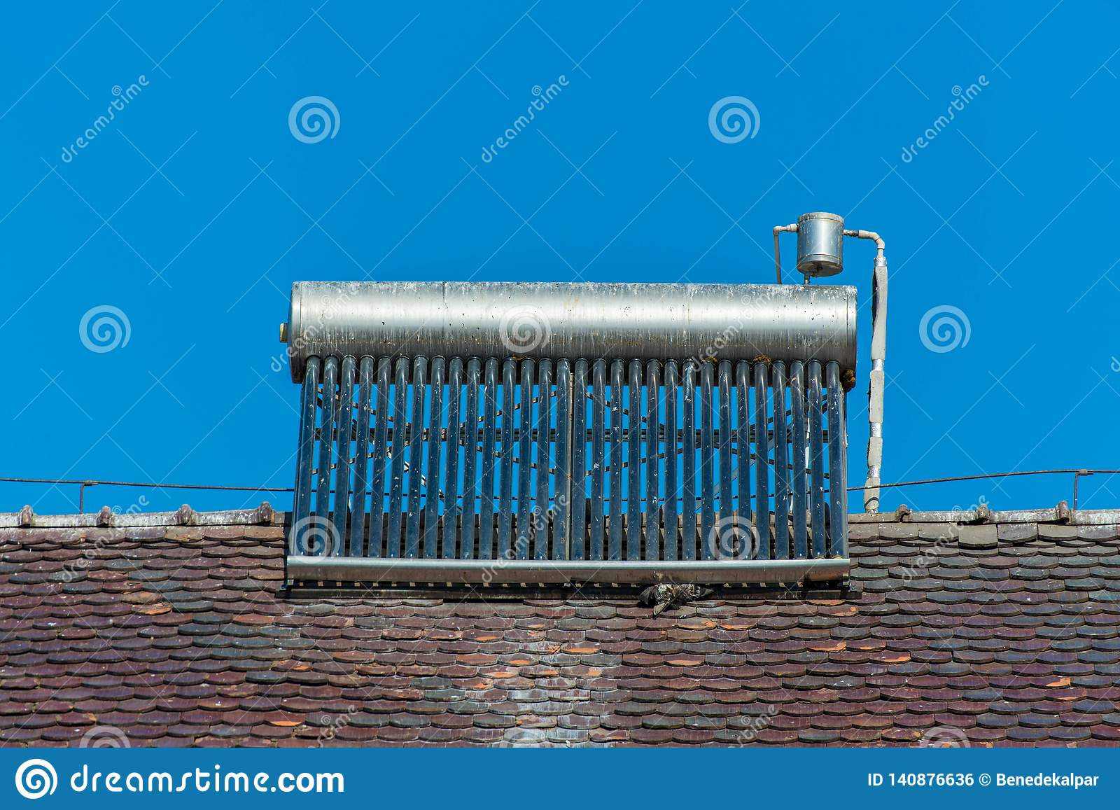 Solar water heater boiler on rooftop, visible bird excrements