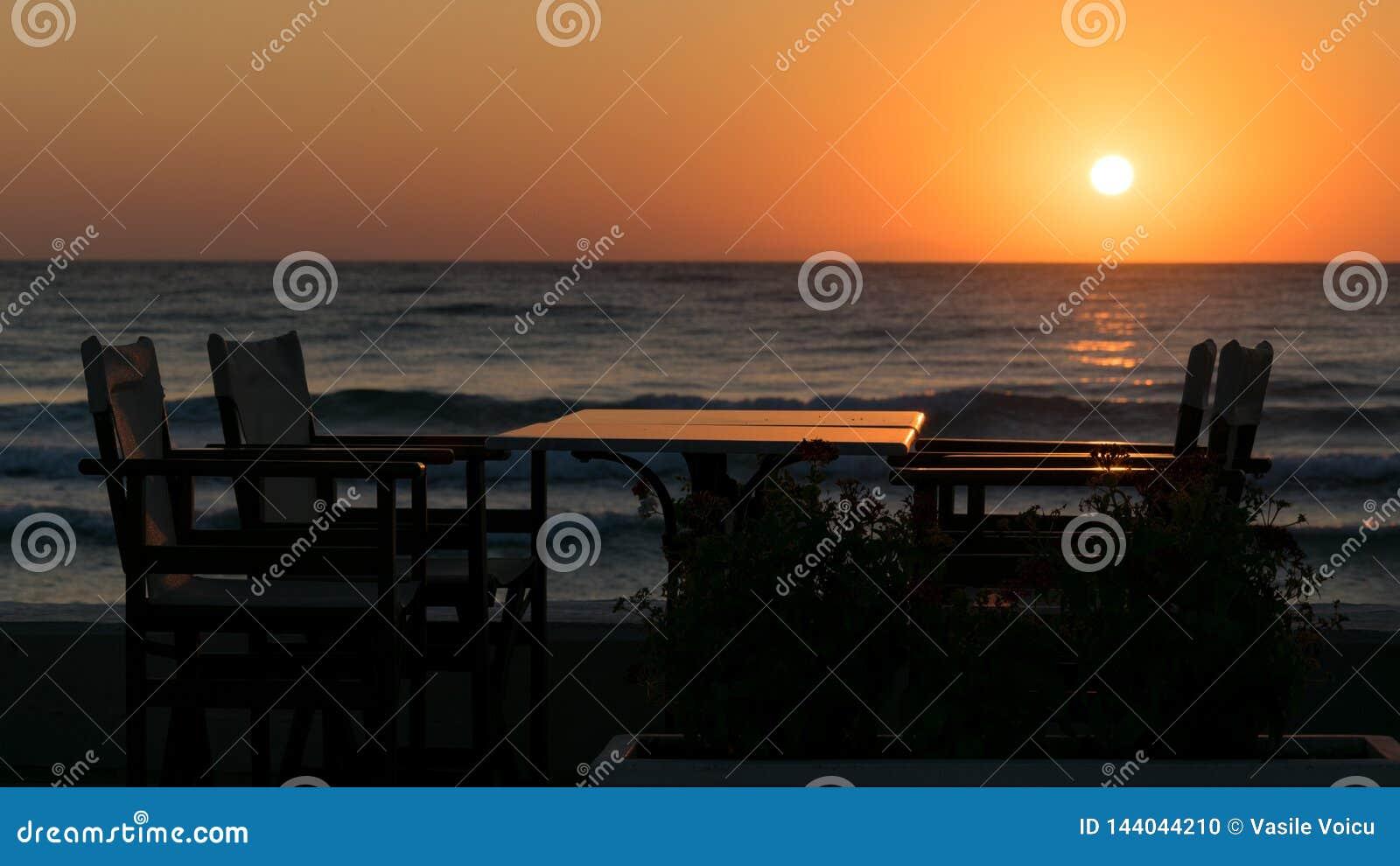 Solbada på stranden med konturn för placering och för äta middag tabell för frukost och havet med vågor