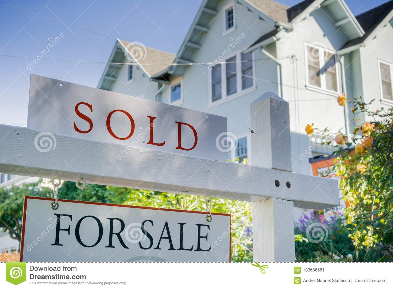 Sold sign in front of a house in a residential neighborhood