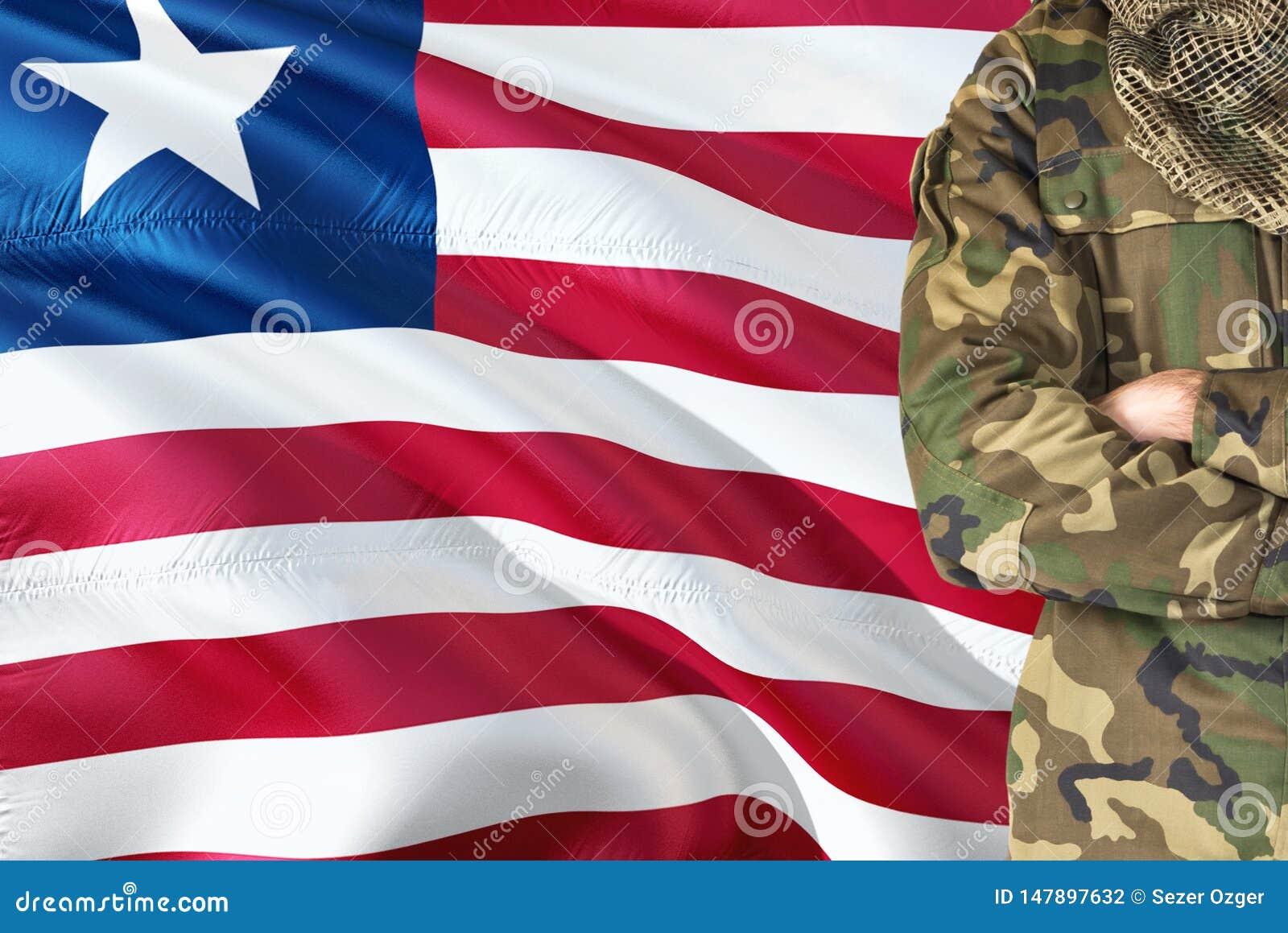 Soldado liberiano cruzado dos braços com a bandeira de ondulação nacional no fundo - tema militar de Libéria