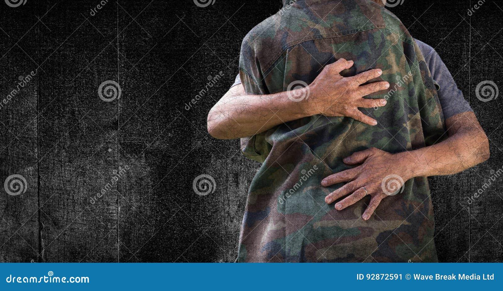 Soldado que abraça a seção meados de contra o painel e a folha de prova de madeira pretos do grunge