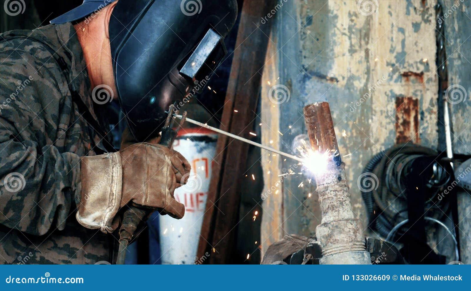 Soldador na fábrica nas peças de metal de solda das soldas da máscara Quadro Peças de solda mascaradas do soldador Soldadura com
