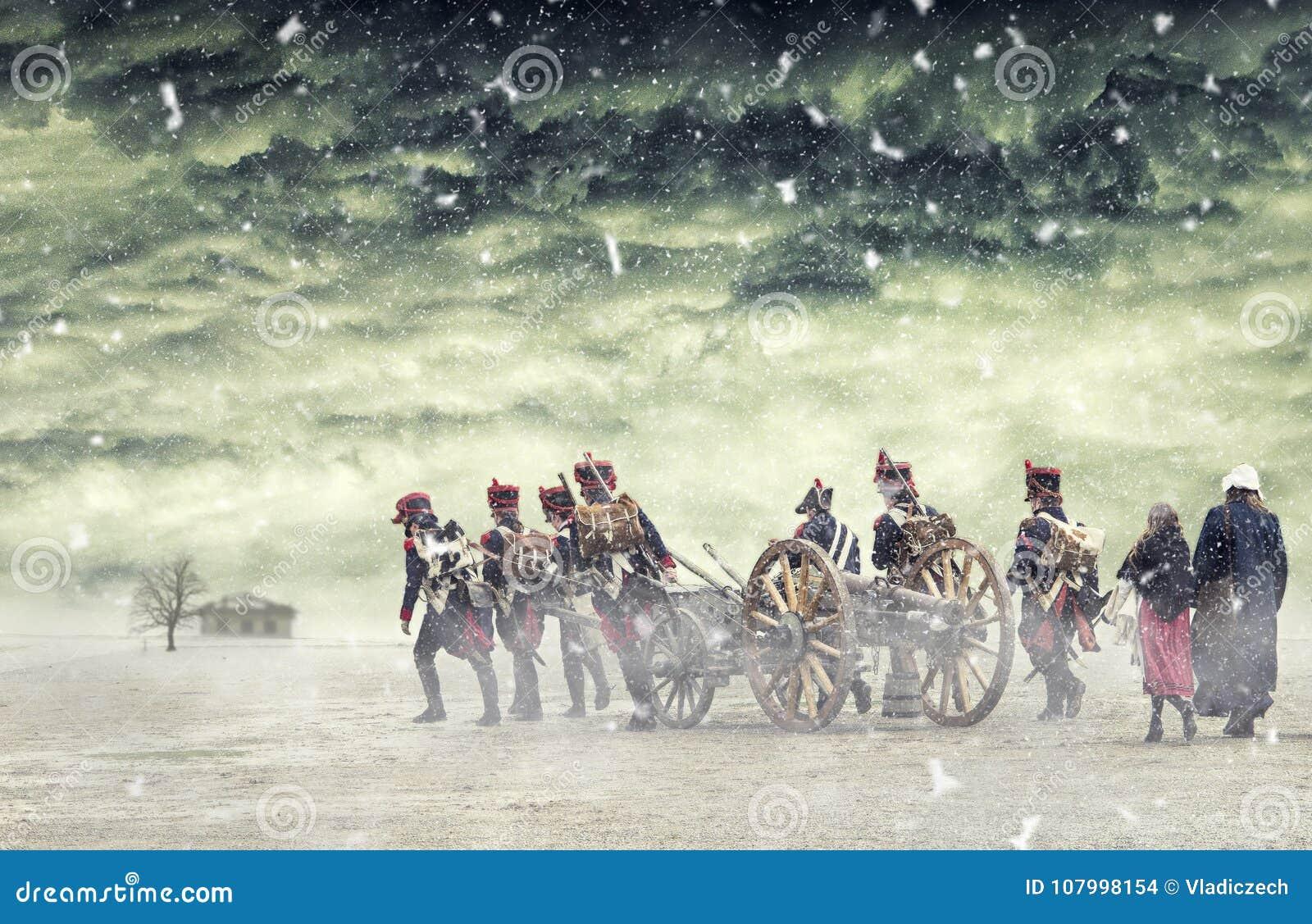 Soldados de Napoleão e mulheres que marcham na neve de queda e que puxam um canhão na terra lisa, campo com nuvens tormentosos so