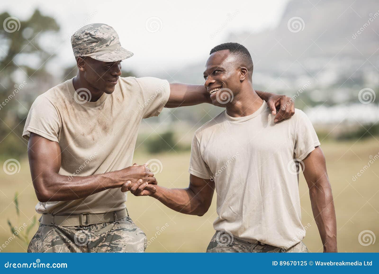 Soldados militares que agitam as mãos durante o curso de obstáculo