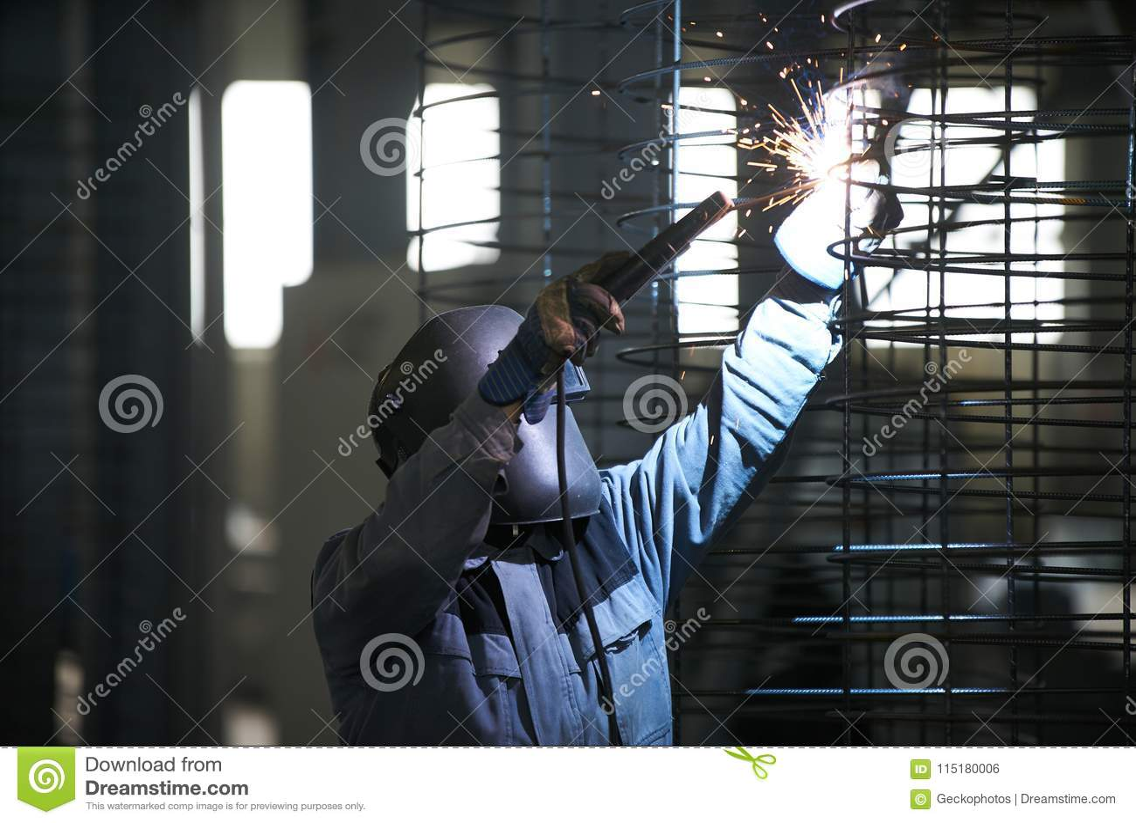 Soldas do homem do soldador na fábrica