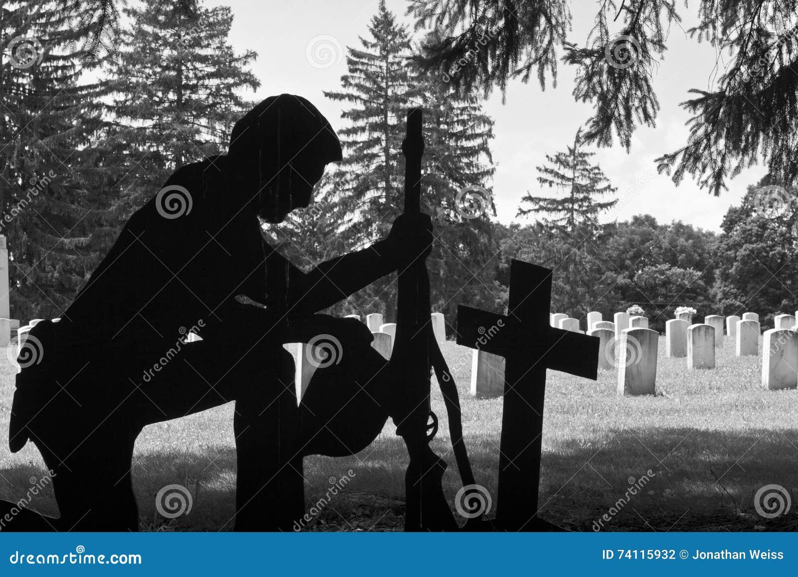 Soldat à genoux à côté de la croix de bataille d un camarade tombé près des pierres tombales I
