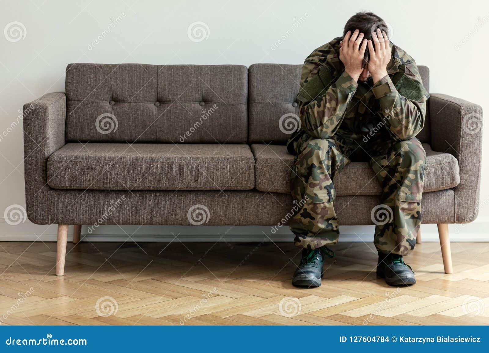 Soldat déprimé dans l uniforme vert avec le syndrome de guerre sur le sofa wainting pour le thérapeute