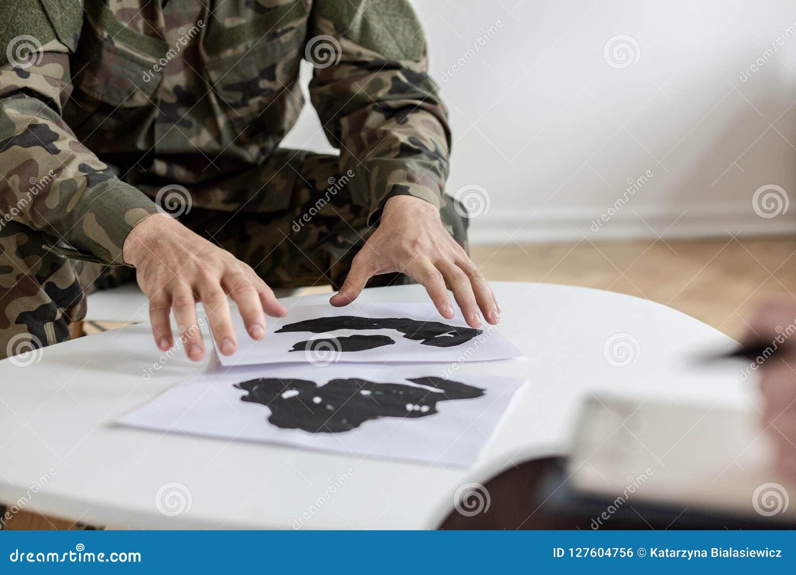 Soldat dans l uniforme vert de moro choisissant des photos pendant la thérapie avec le psychiatre