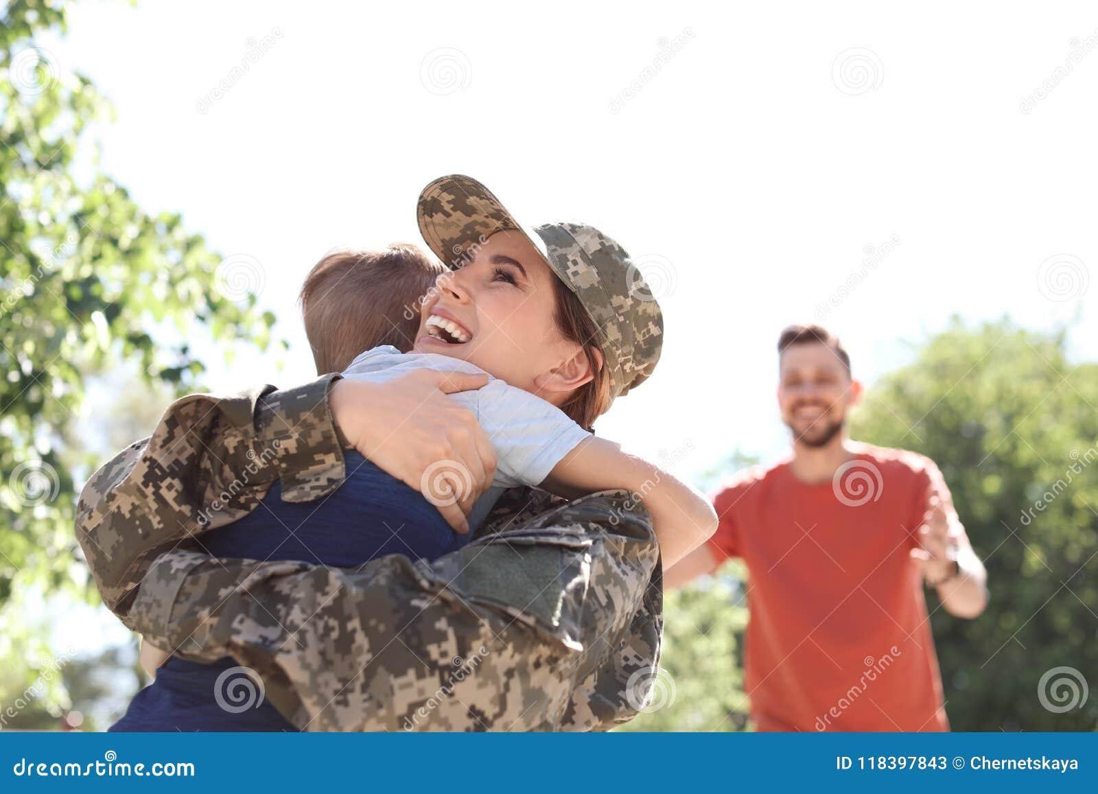 Soldat féminin étreignant avec son fils, dehors Service militaire