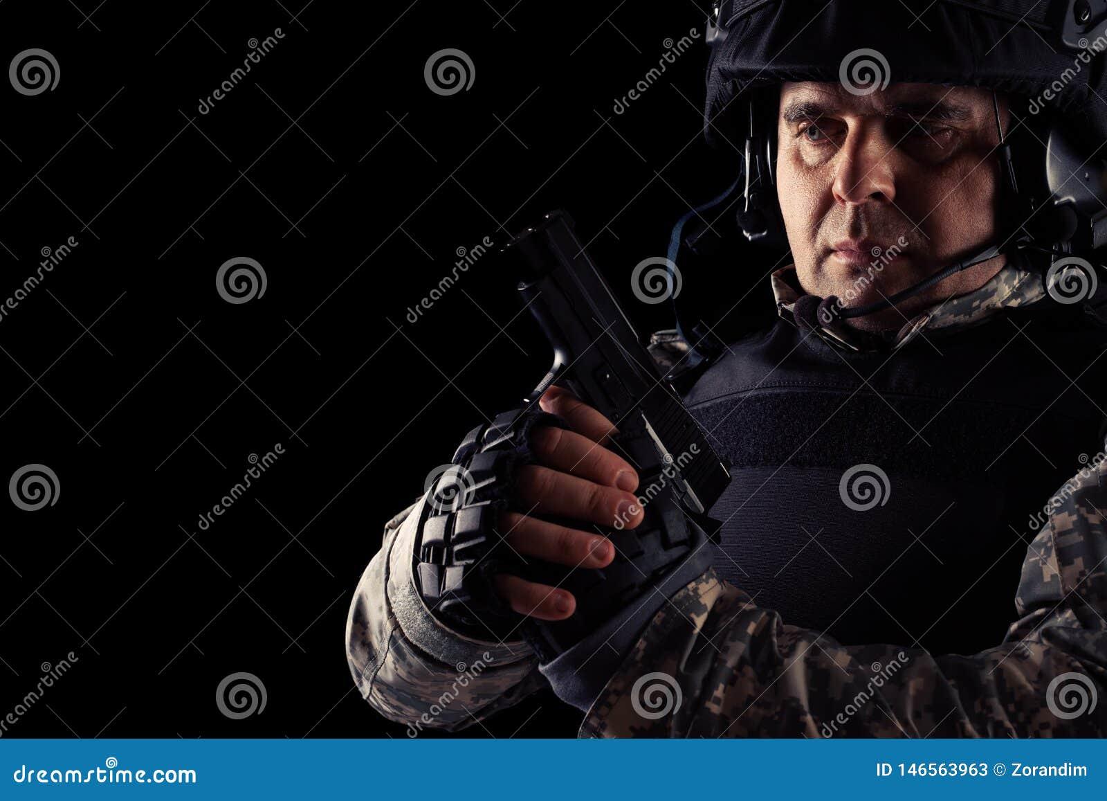 Soldat visant avec le pistolet noir image sur un fond fonc?