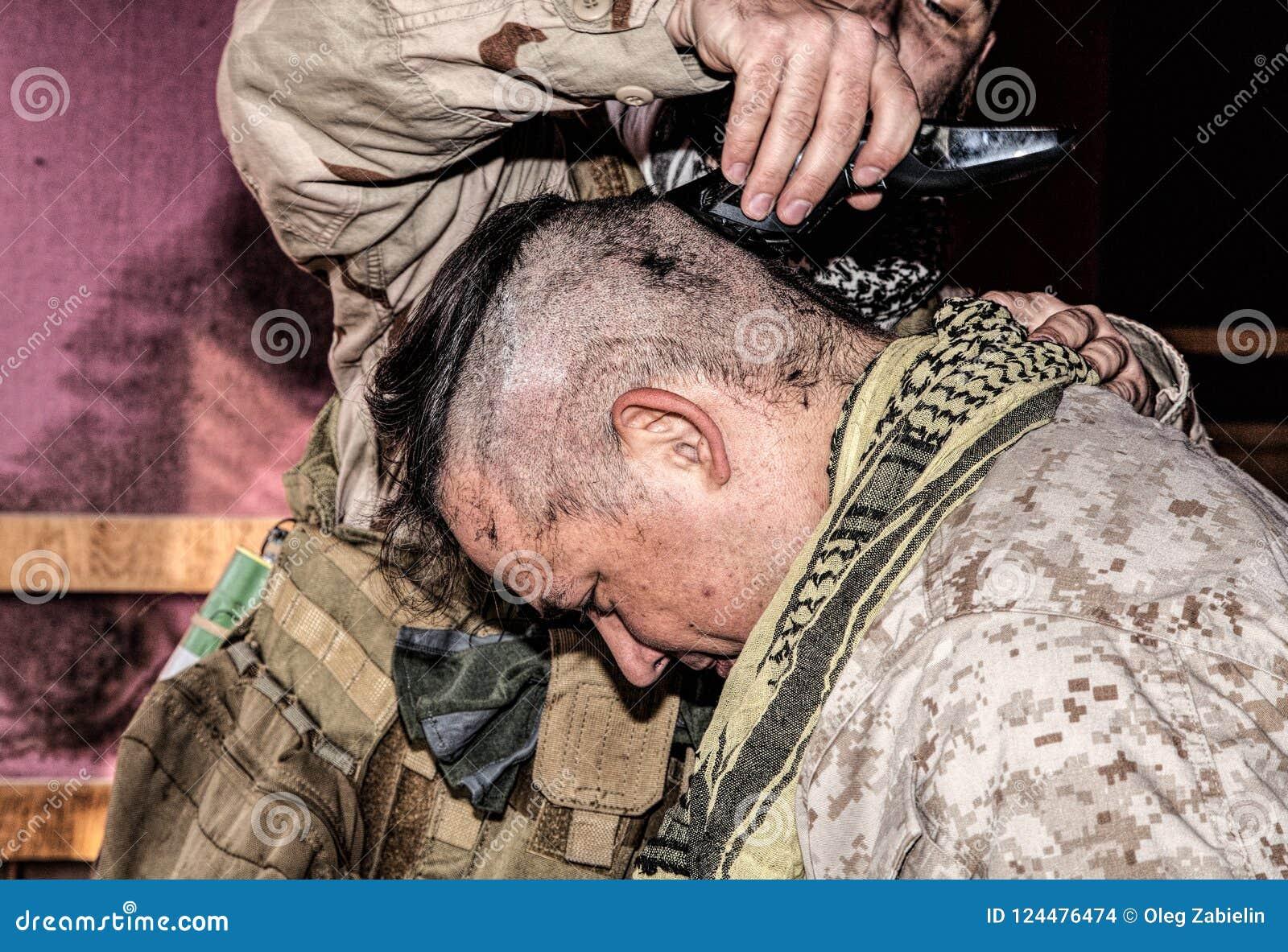 Soldaten klipper kamrathår med beskäraren eller clipperen