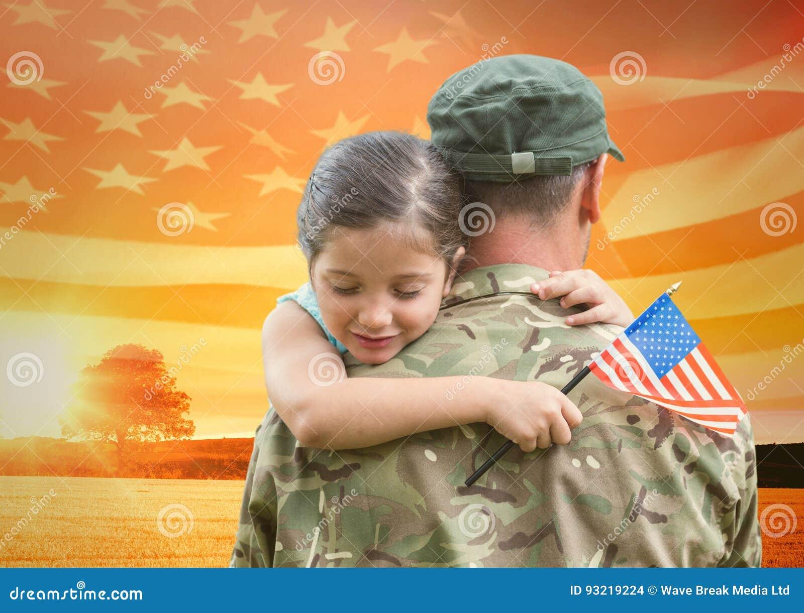 Soldato che abbraccia figlia nel campo con la bandiera degli S.U.A.