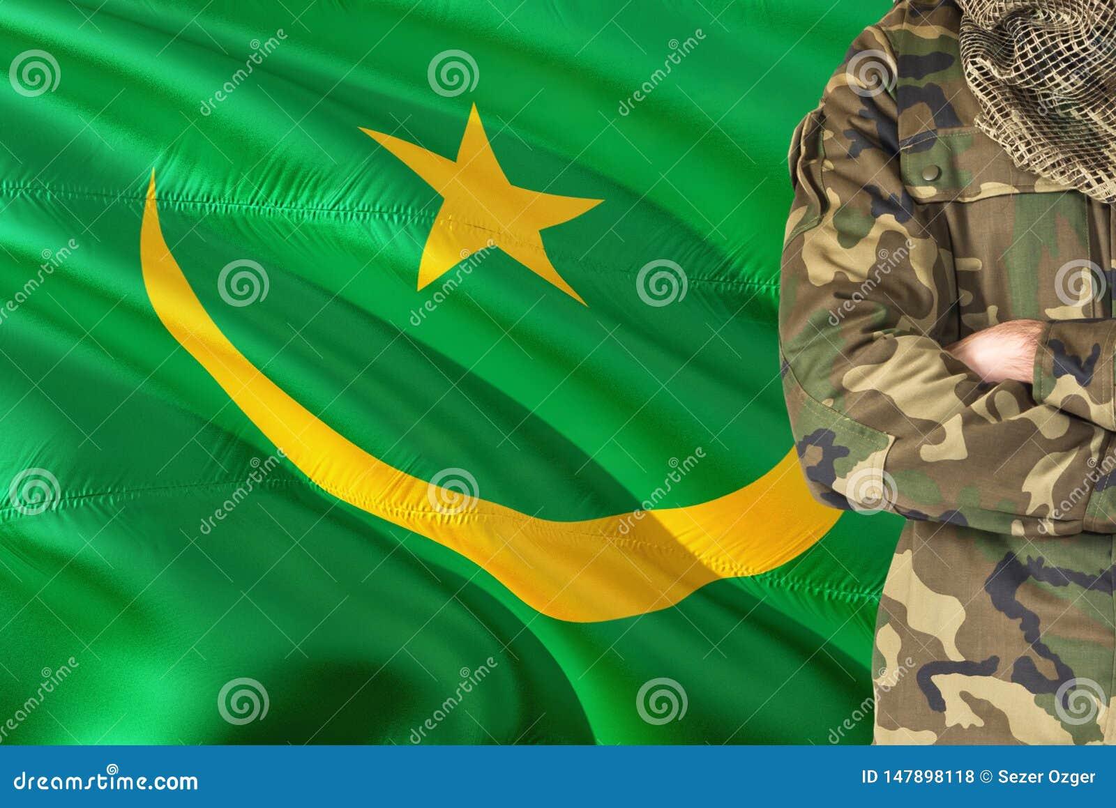 Soldato mauritaniano attraversato di armi con la bandiera d ondeggiamento nazionale su fondo - tema militare della Mauritania