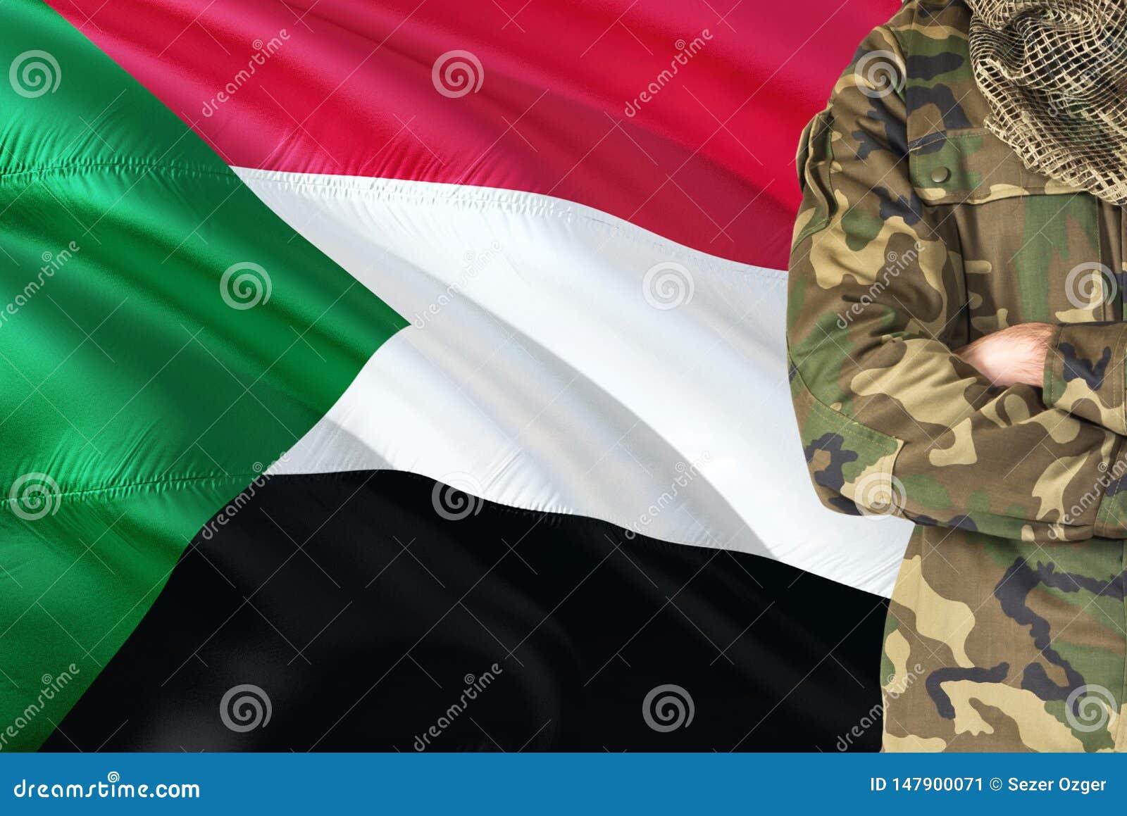 Soldato sudanese attraversato di armi con la bandiera d ondeggiamento nazionale su fondo - tema militare del Sudan
