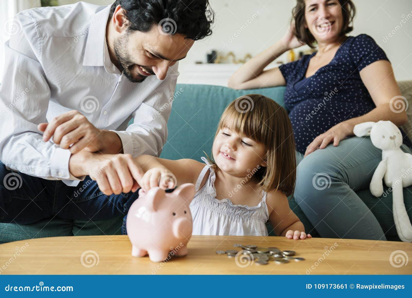 Soldi di risparmio della famiglia in porcellino salvadanaio