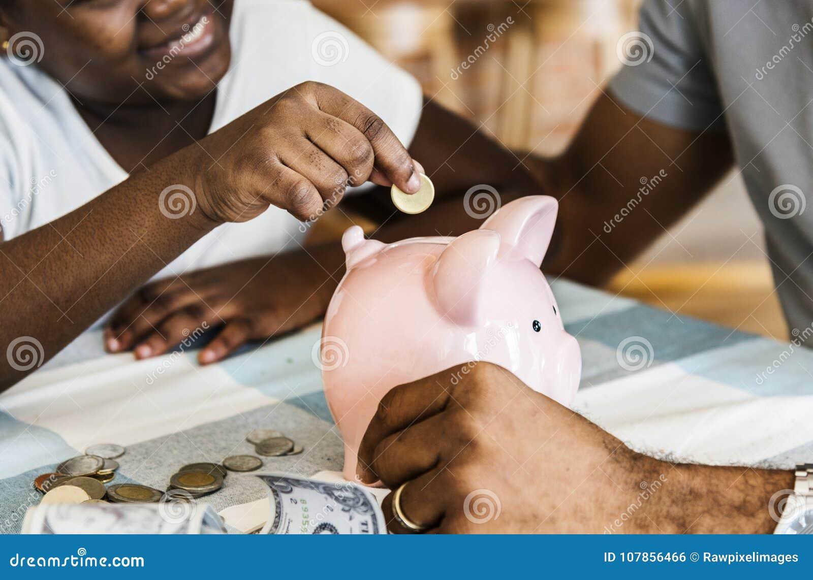 Soldi di risparmio della figlia e del papà al porcellino salvadanaio