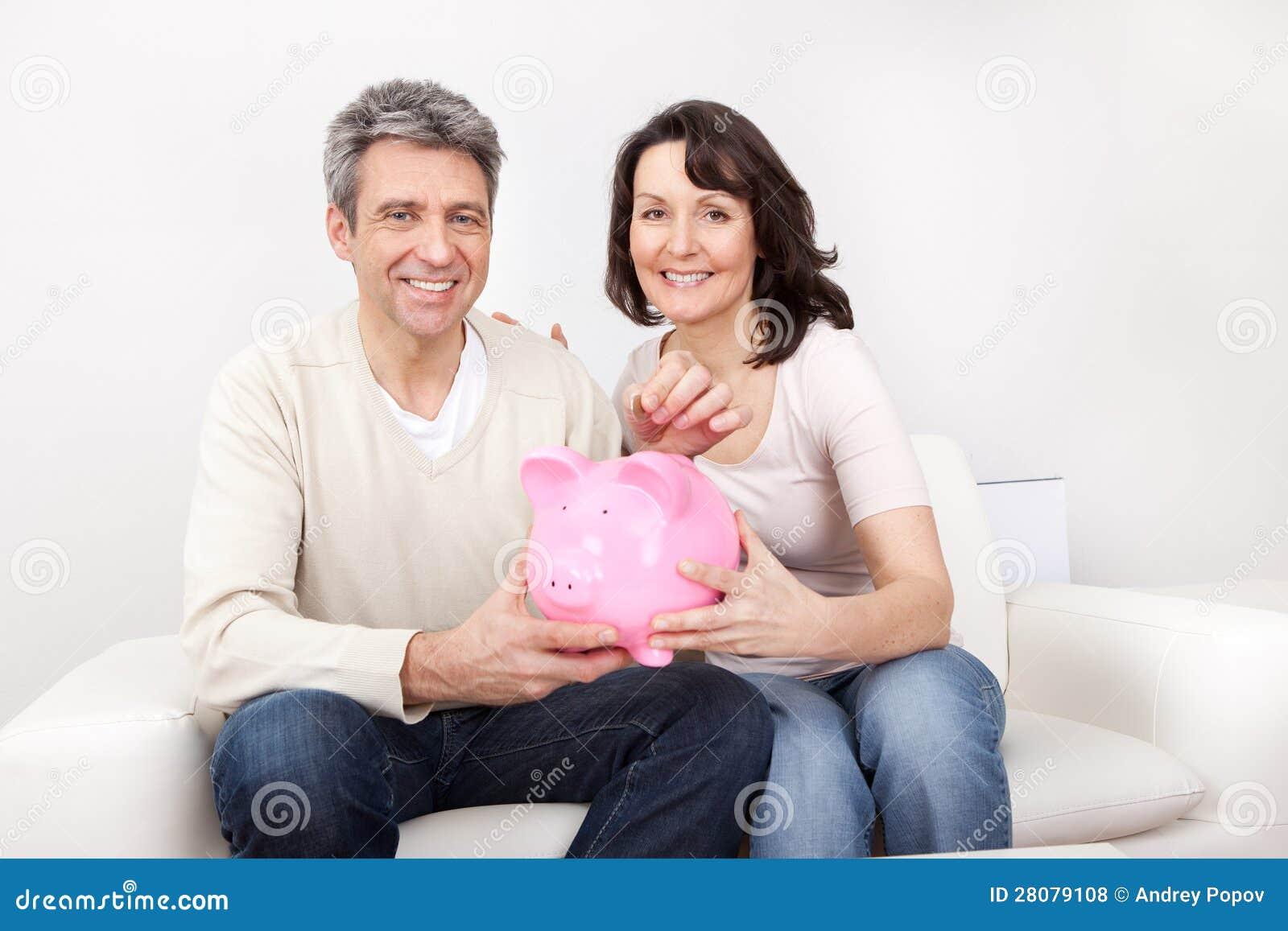 Soldi maturi di risparmio delle coppie in porcellino salvadanaio