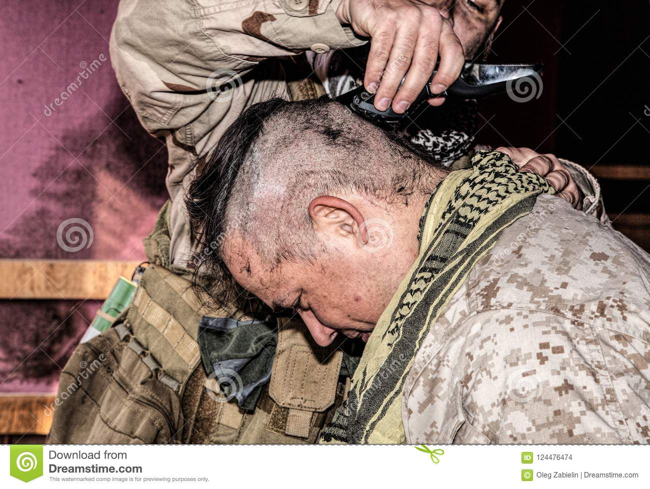 Soldier cuts comrades hair with trimmer or clipper