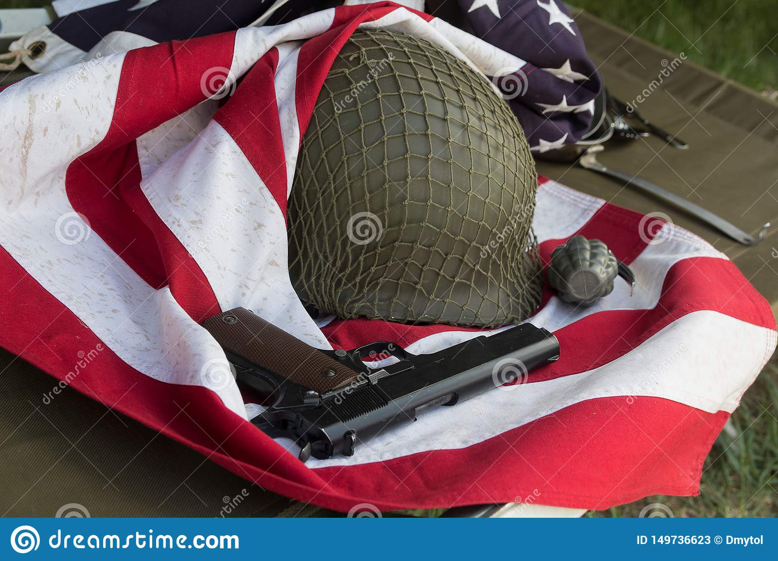 Soldier helmet, pistolt and grenade from the Second World War and the flag of the USA