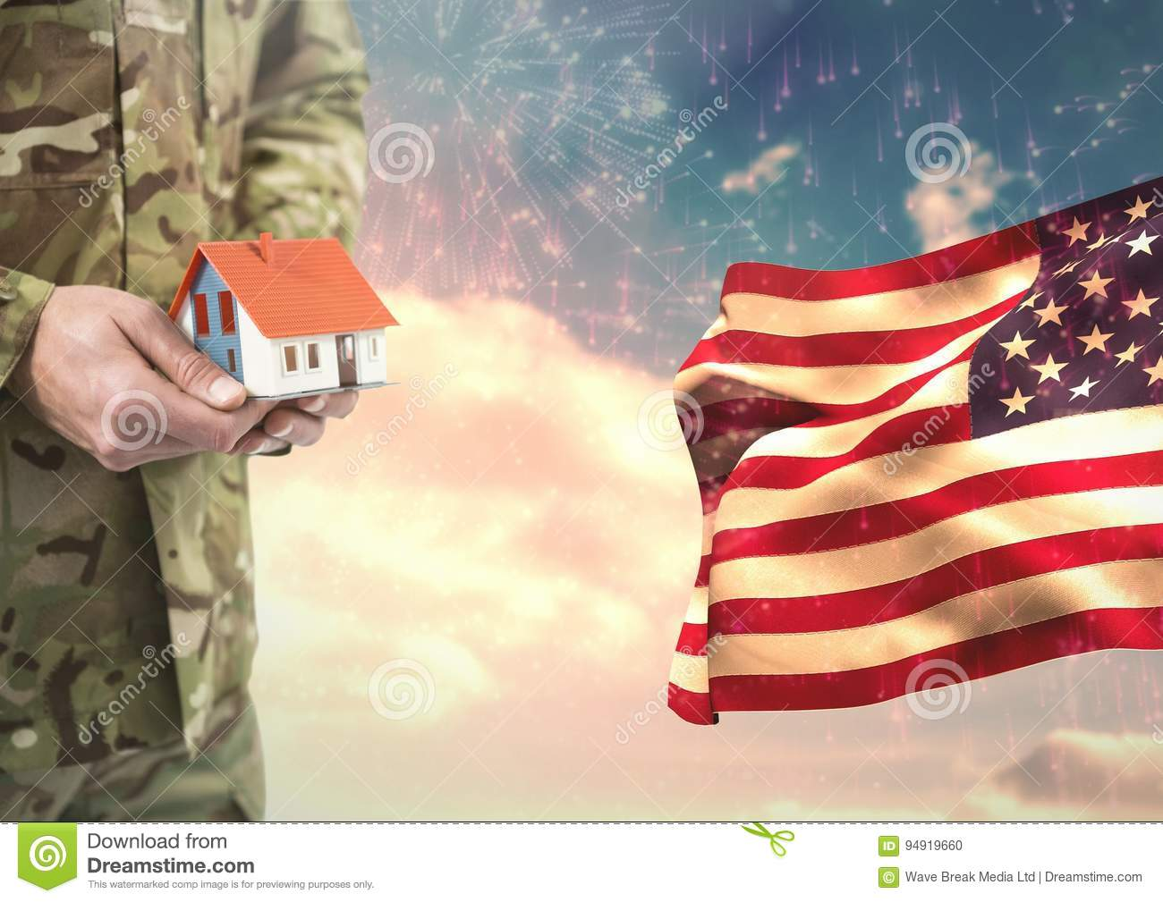 Soldier holding a little house close to the american flag