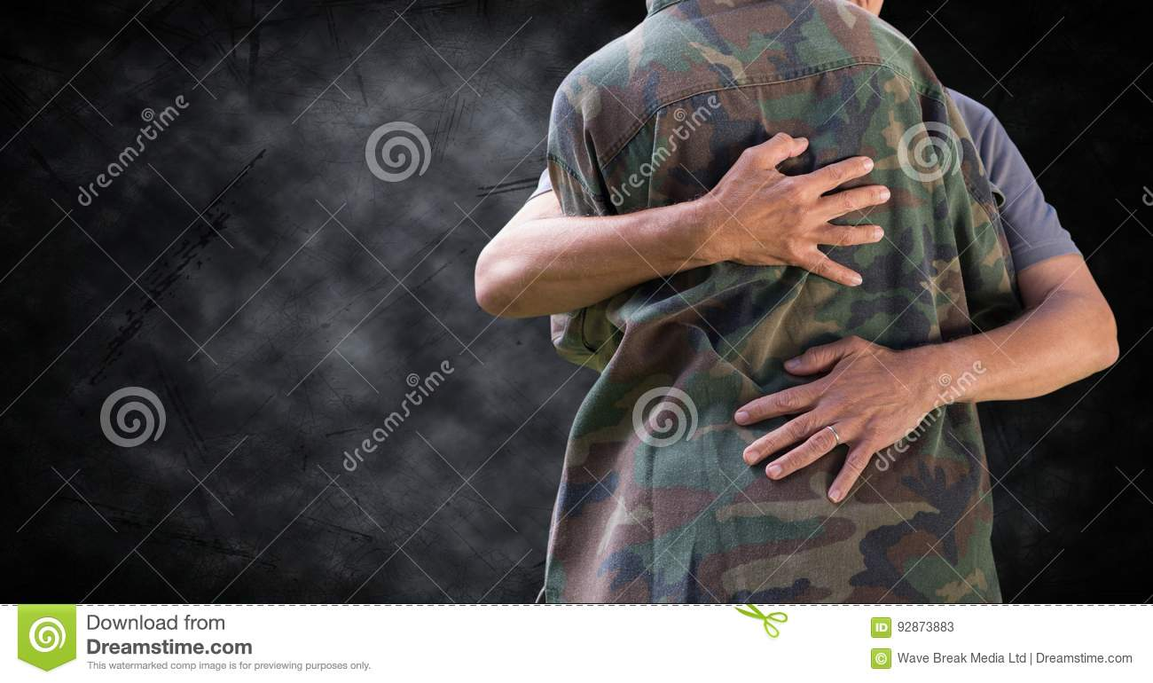 Soldier hugging mid section against black grunge background