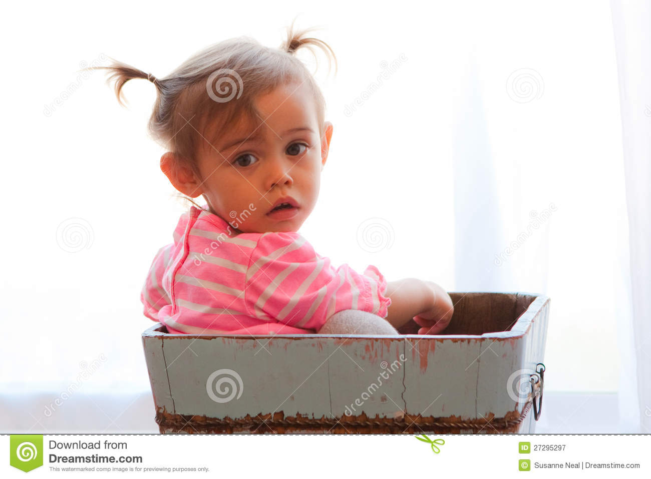 Solemn baby girl in wooden box royalty free stock photography image