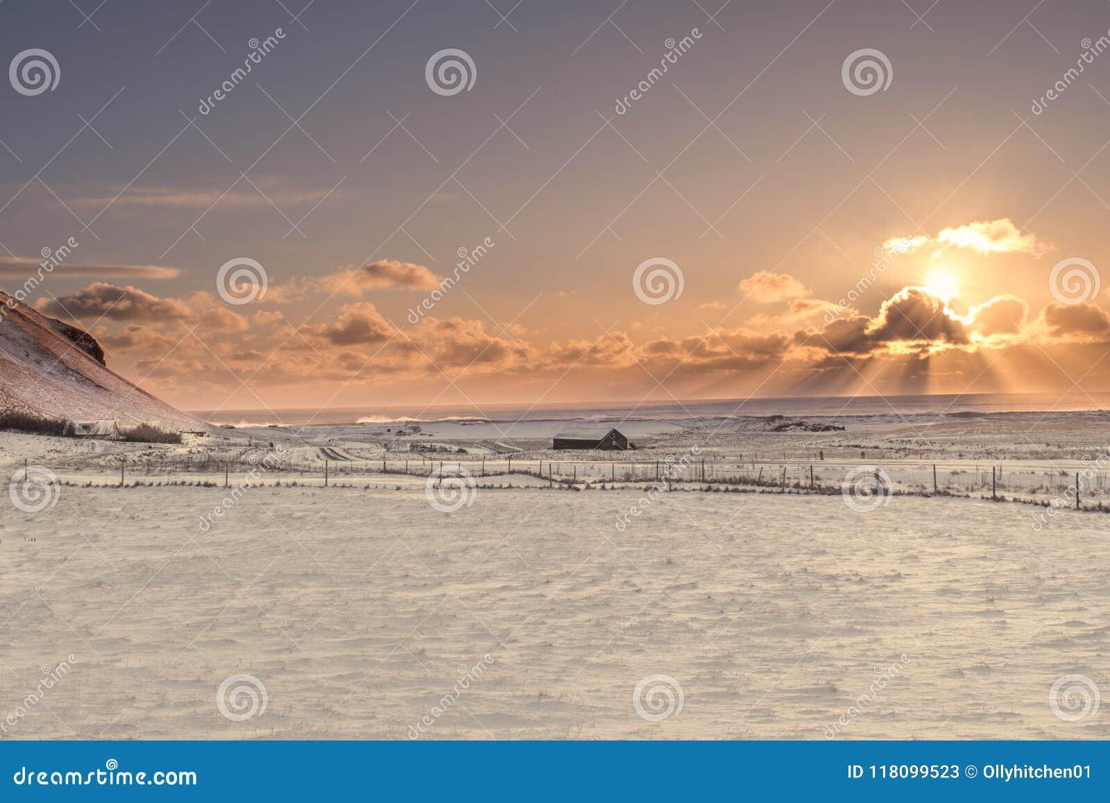 Solen brister bakifrån ett moln över det djupfrysta landskapet av