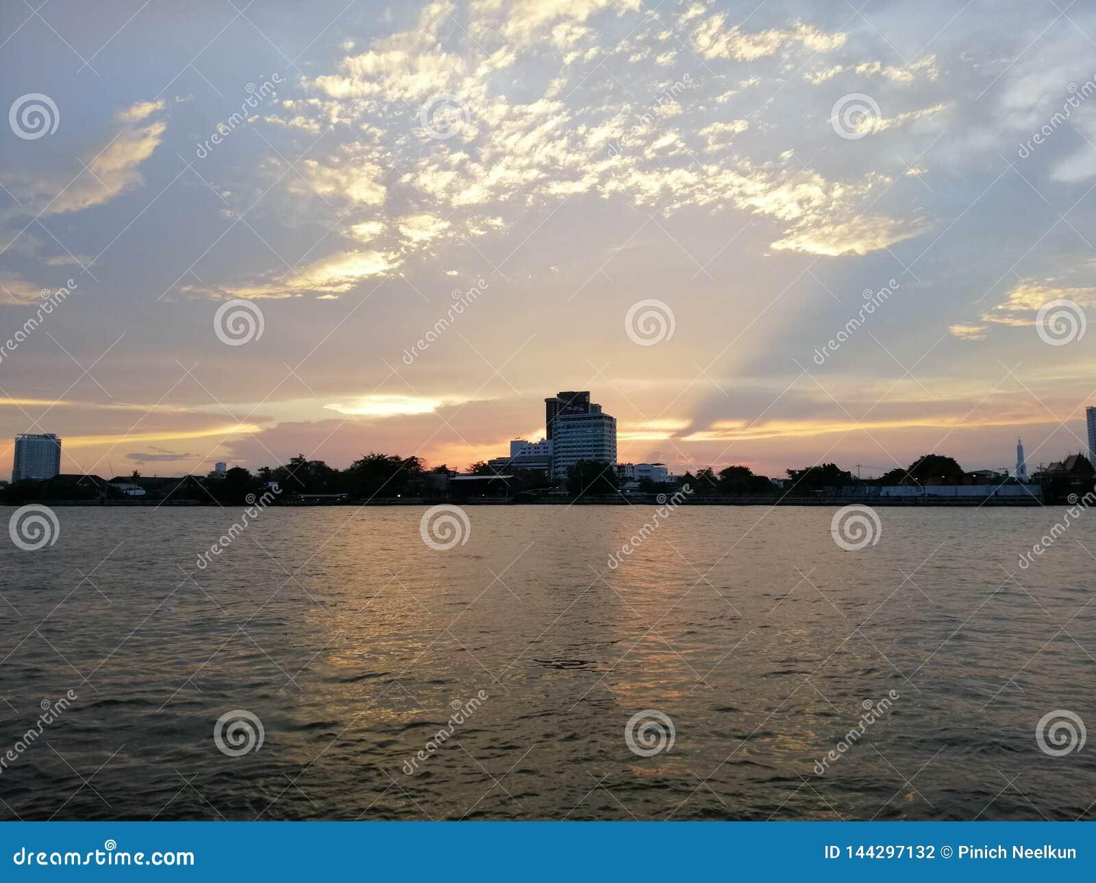 Solen ställer in på bankerna av Chao Phraya River - Wat Kretkrai, Bangkok-Thailand