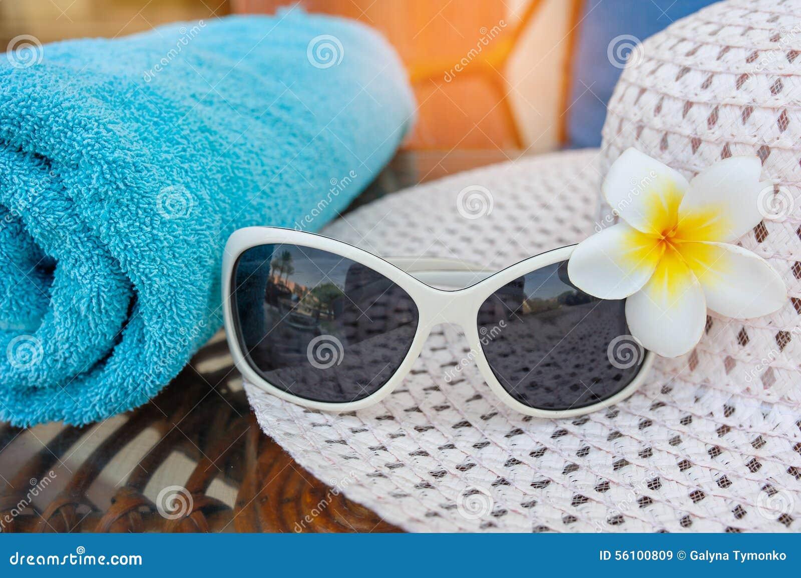 Solglasögon är på hatten och blomman på stranden
