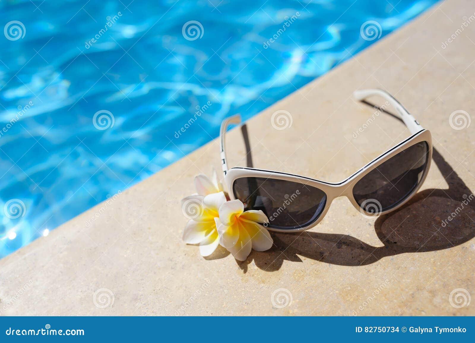 Solglasögon och vita blommor av den near pölen för bougainvillea